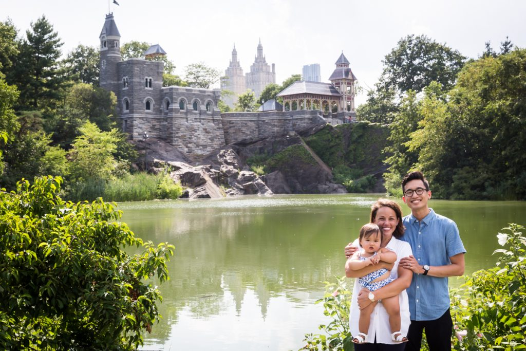 Mother and father holding baby in front of Turtle Pond and Belvedere Castle