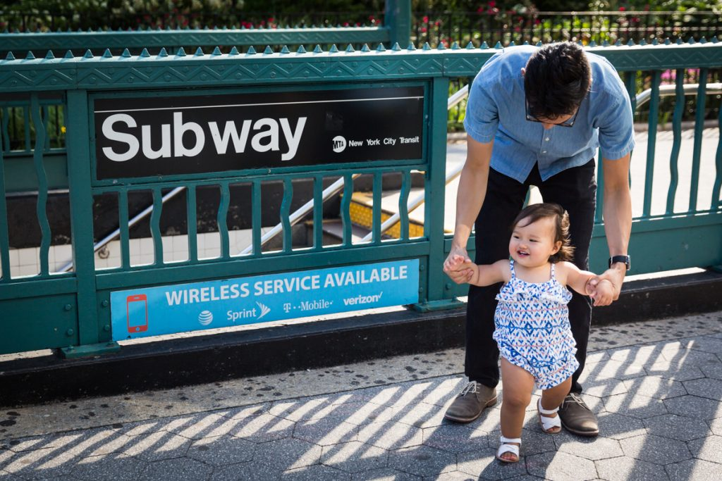 Father holding baby by hand in front of NYC subway sign