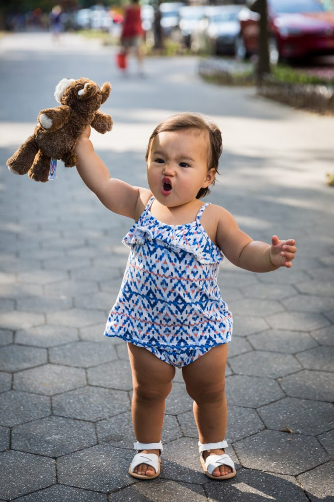 Little girl making funny face and holding up stuffed animal