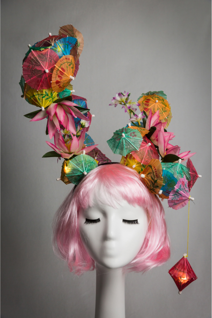 Pink haired mannequin wearing tiki cocktail umbrella headband that lights up