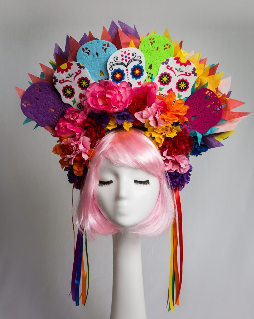 Pink haired mannequin wearing colorful floral Day of the Dead headband