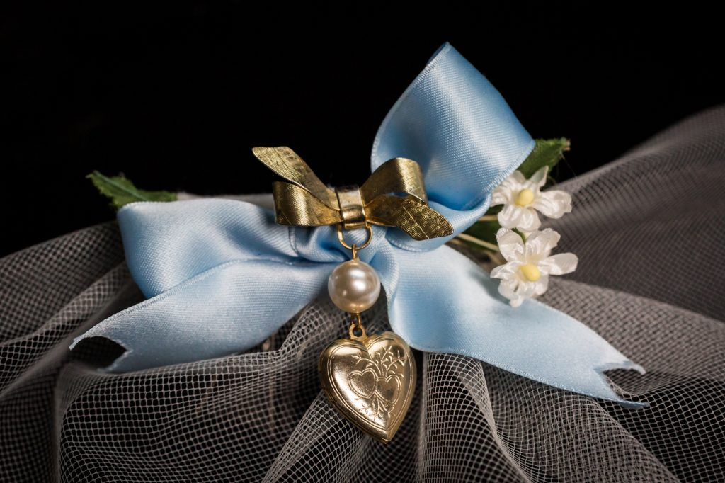 Close up on bridal veil with blue bow and heart locket