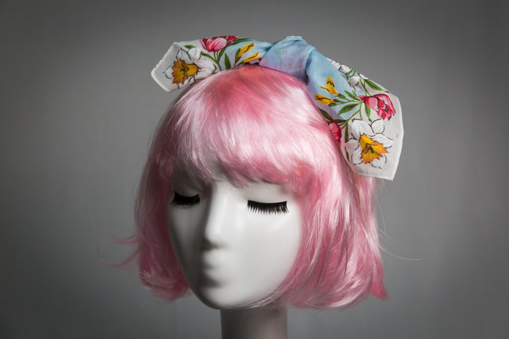 Pink haired mannequin wearing light blue and floral tied fabric headband