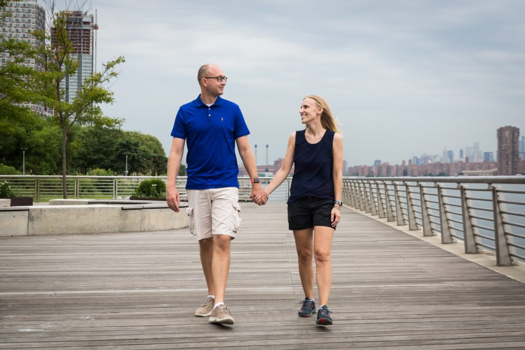 Couple holding hands and walking along Gantry Plaza State Park boardwalk