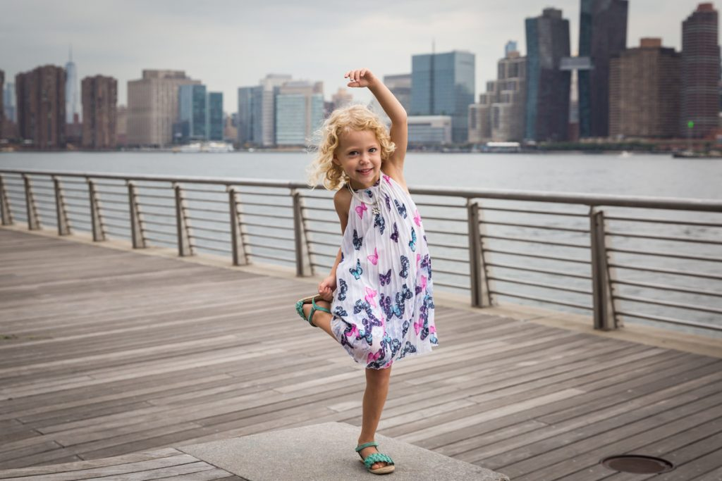 Little girl with blond hair holding foot during a Gantry Plaza family portrait session