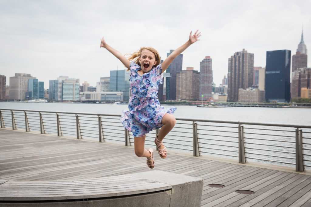 Little girl jumping on boardwalk during a Gantry Plaza family portrait session