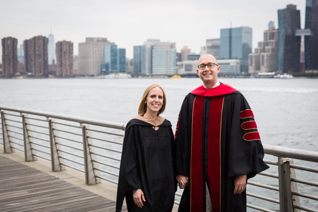 Couple dressed in graduation robes on boardwalk during a Gantry Plaza family portrait session