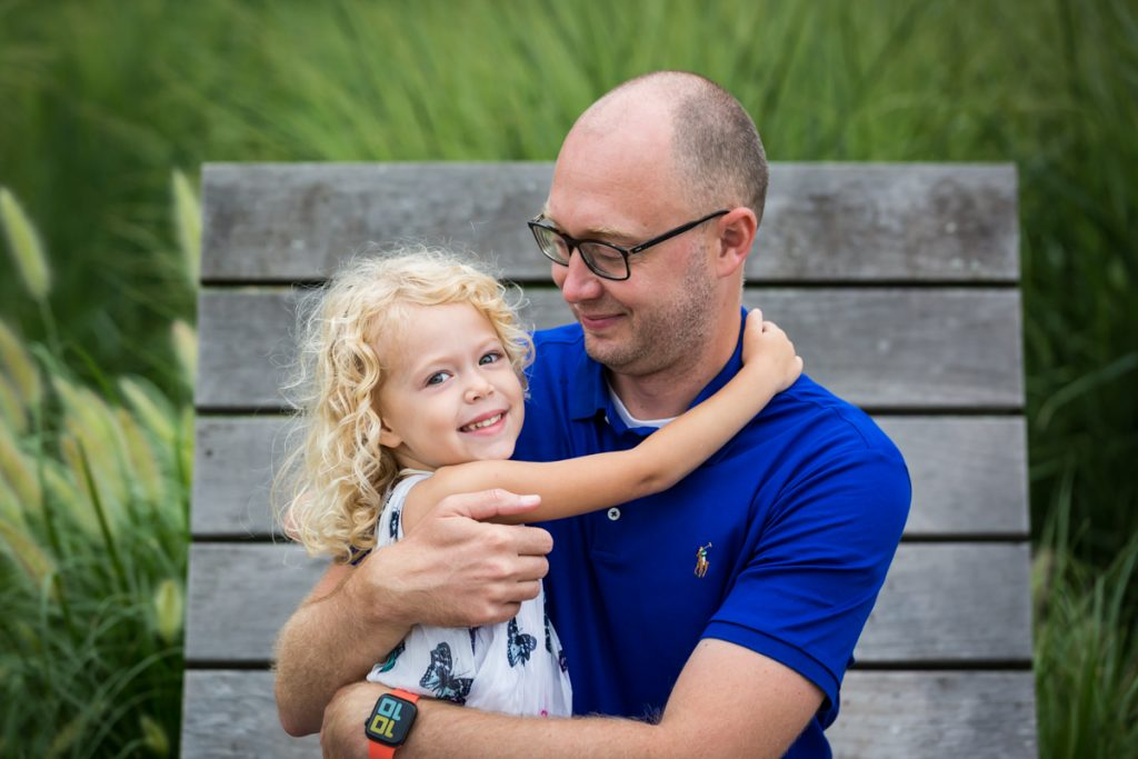 Blond haired girl hugging daddy on wooden chair