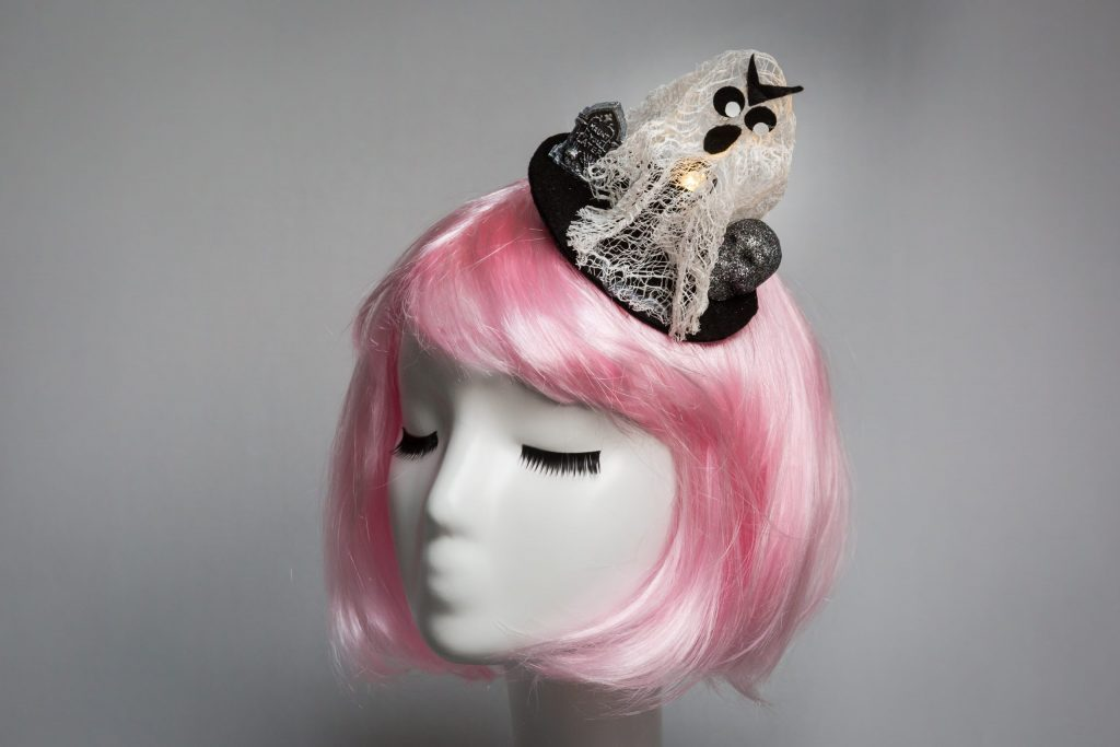 Pink haired mannequin wearing cheesecloth ghost fascinator that lights up