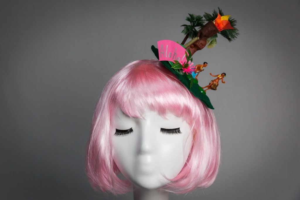 Pink haired mannequin wearing tiki Hawaii fascinator with hula girls