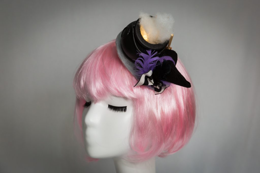 Pink haired mannequin wearing witch cauldron fascinator that lights up