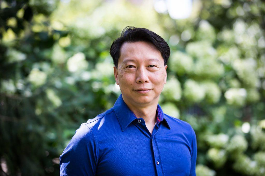 Asian man wearing blue shirt during Washington Square Park family portrait