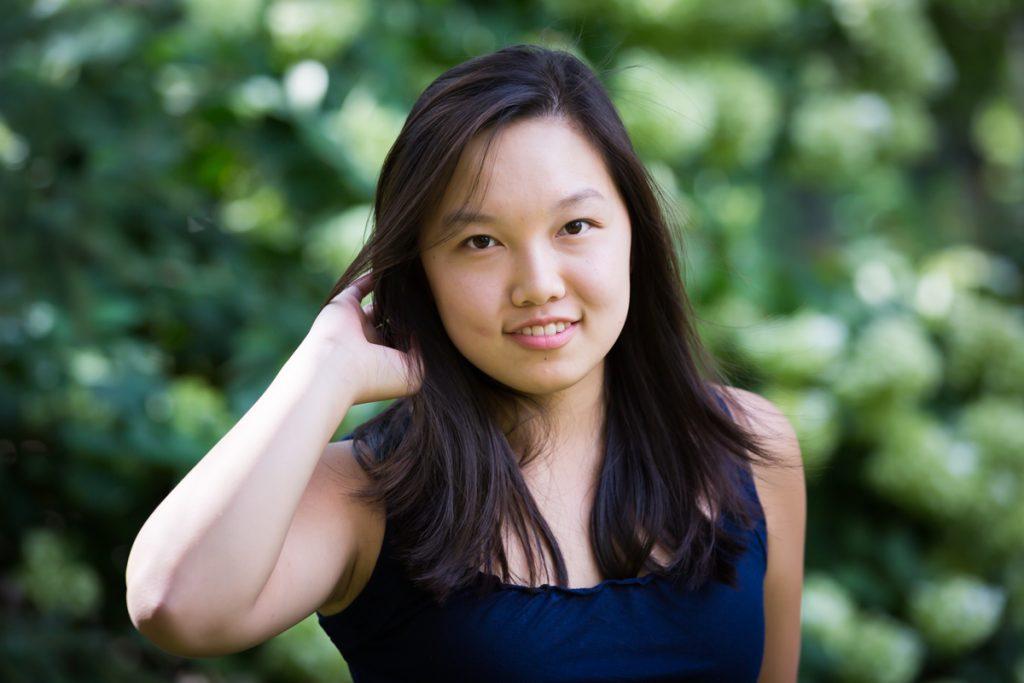 Asian girl touching hair during Washington Square Park family portrait