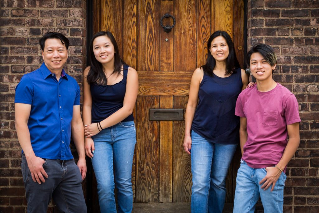 Family standing in front of brick wall and wooden door for an article on photo tips for older children