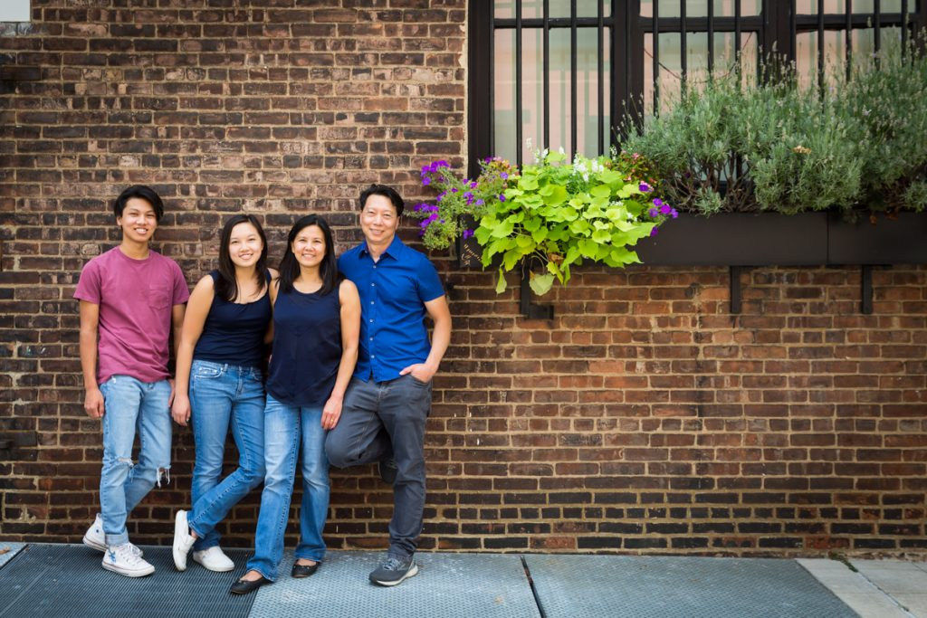 Family standing against brick wall with flowers in window box for an article on photo tips for older children