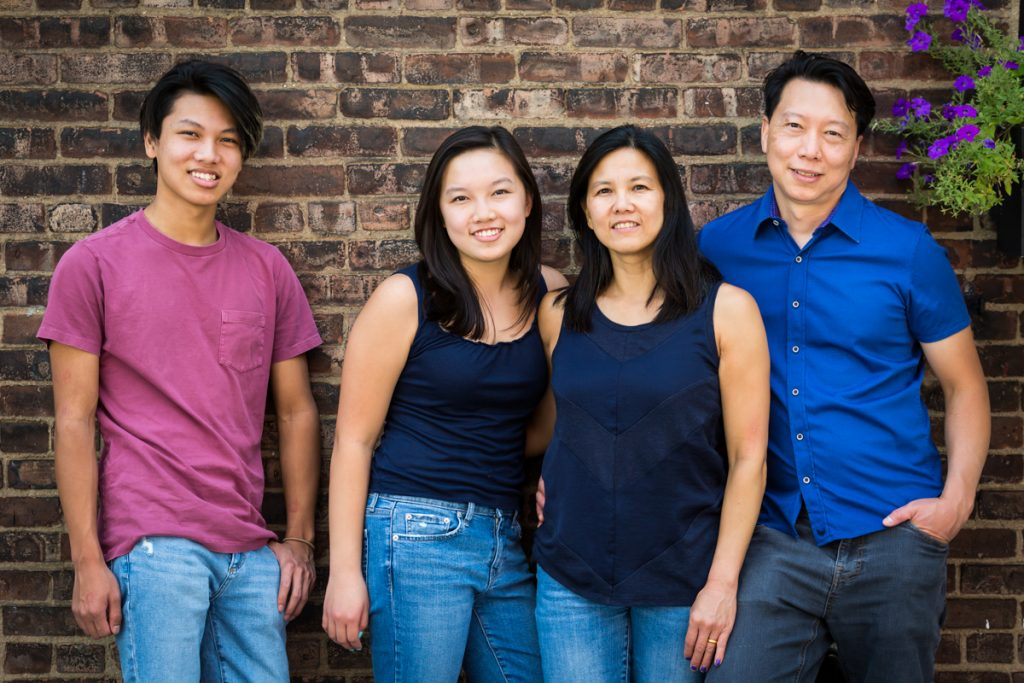 Asian family standing in front of brick wall