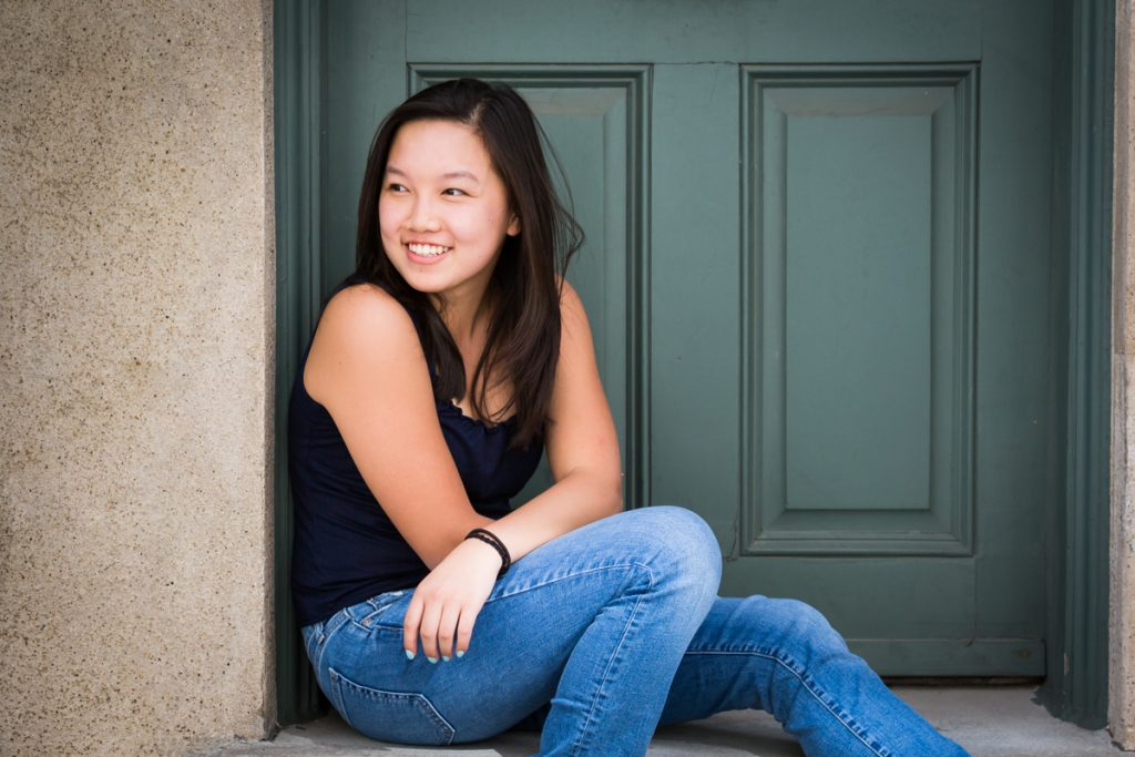 Young woman smiling while sitting in doorway in Washington Mews