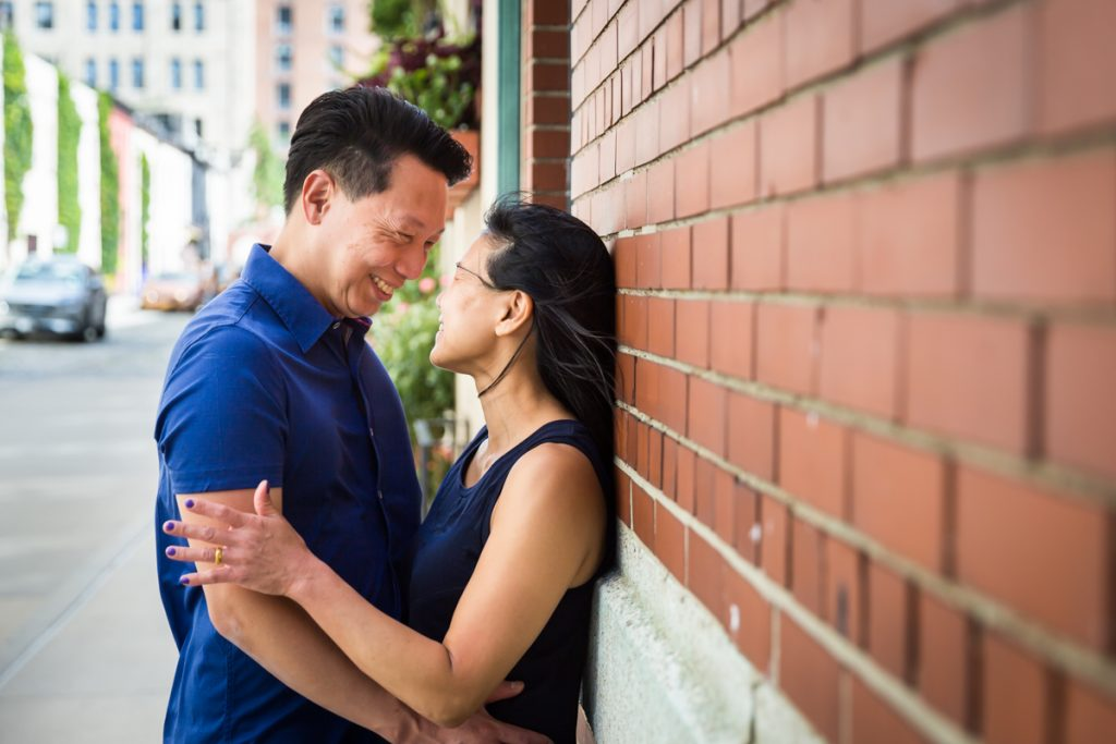 Asian couple hugging against brick wall