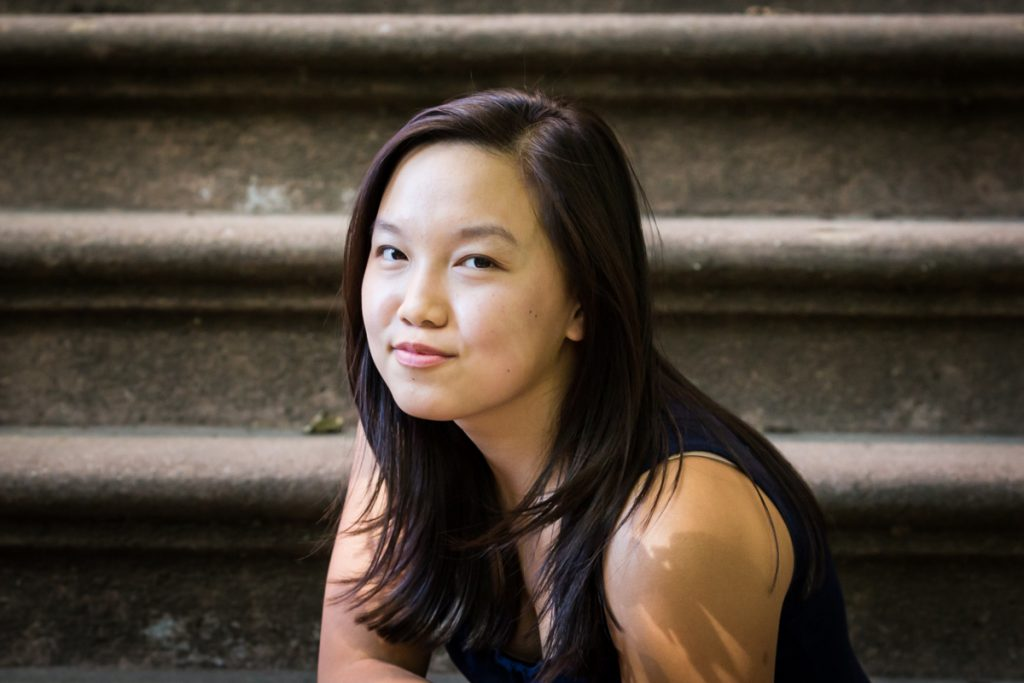 Teenager sitting on brownstone steps for an article on photo tips for older children