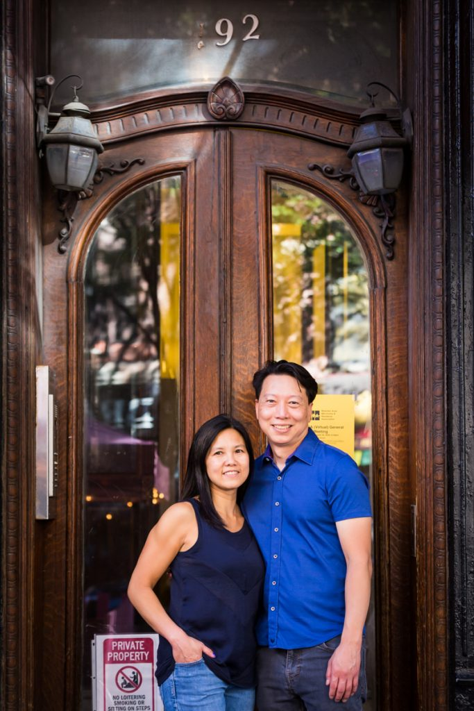 Couple standing in front of wood and glass door in West Village