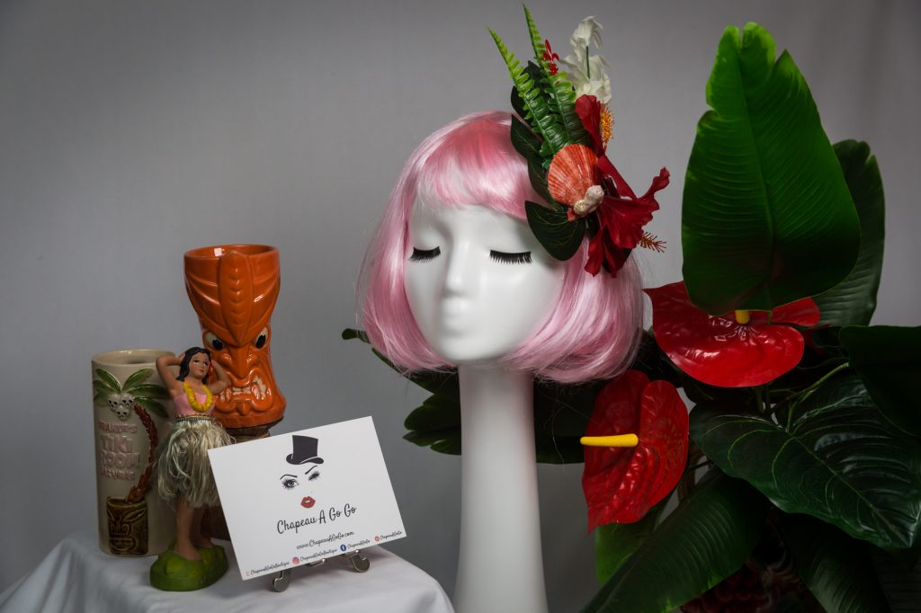 Pink haired mannequin wearing tiki flower hair clip with tiki mugs