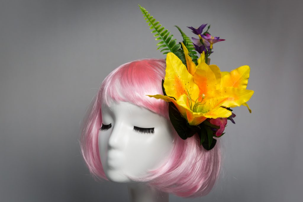 Pink haired mannequin wearing yellow tiki flower hair clip
