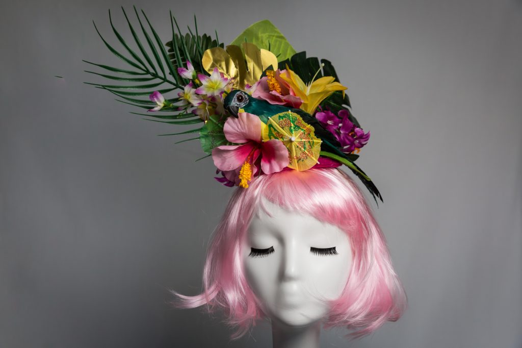 Pink haired mannequin wearing tiki parrot fascinator by Chapeau A Go Go
