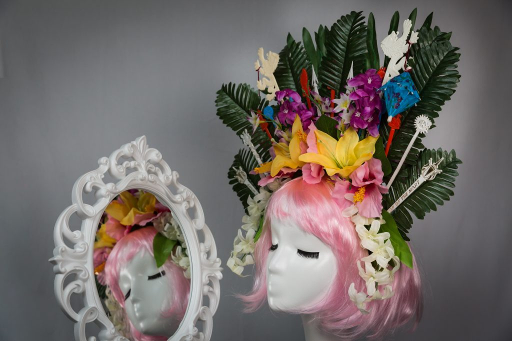 Pink haired mannequin wearing tiki swizzle stick crown reflected in mirror
