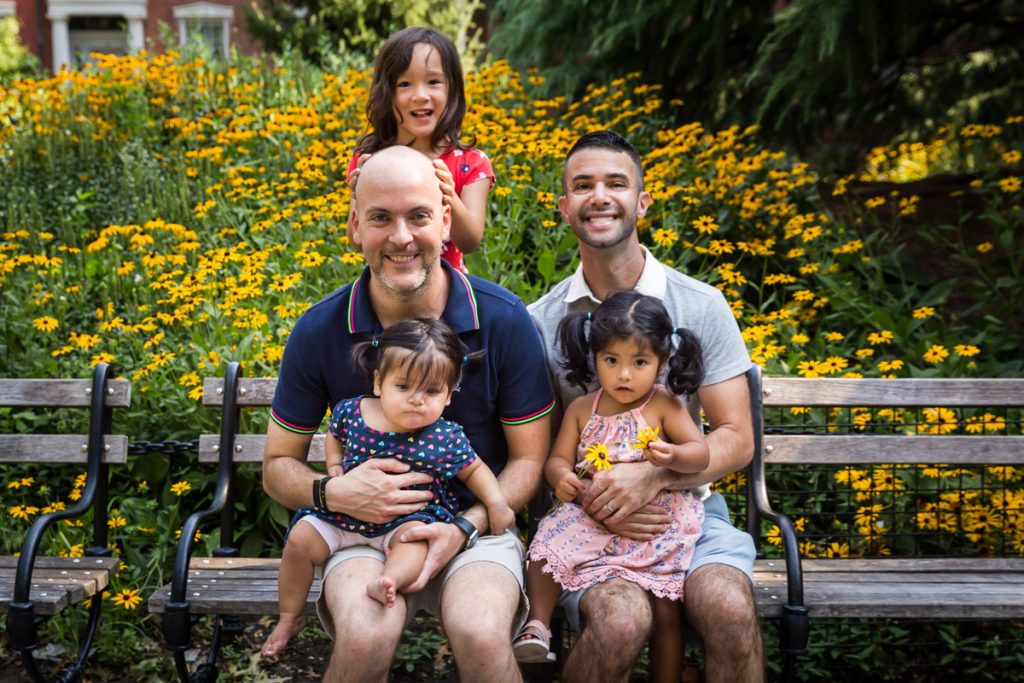 Two fathers and their three daughters sitting on bench during a Washington Square Park family portrait
