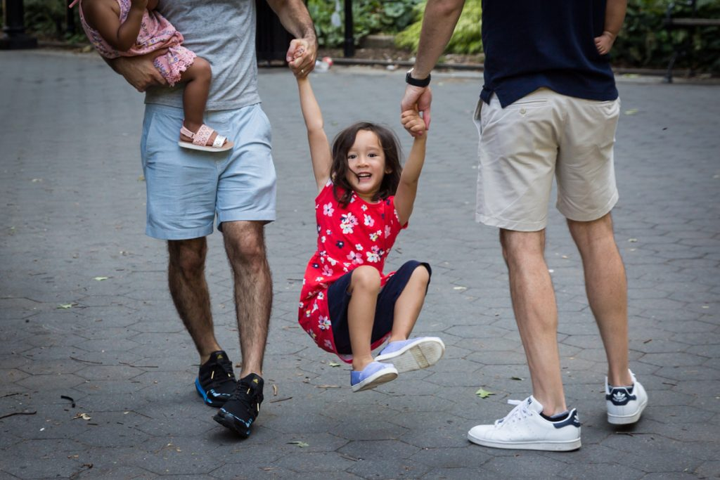 Little girl being swung by arms of two fathers