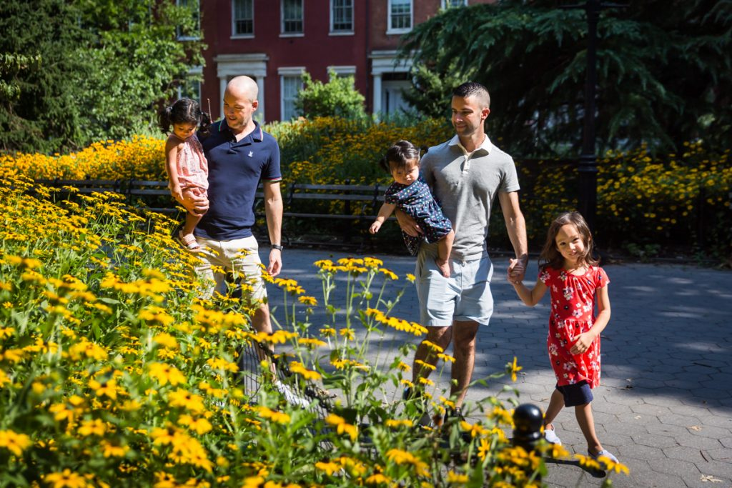 Two fathers and their daughters walking in front of yellow daisies during Washington Square Park family portrait
