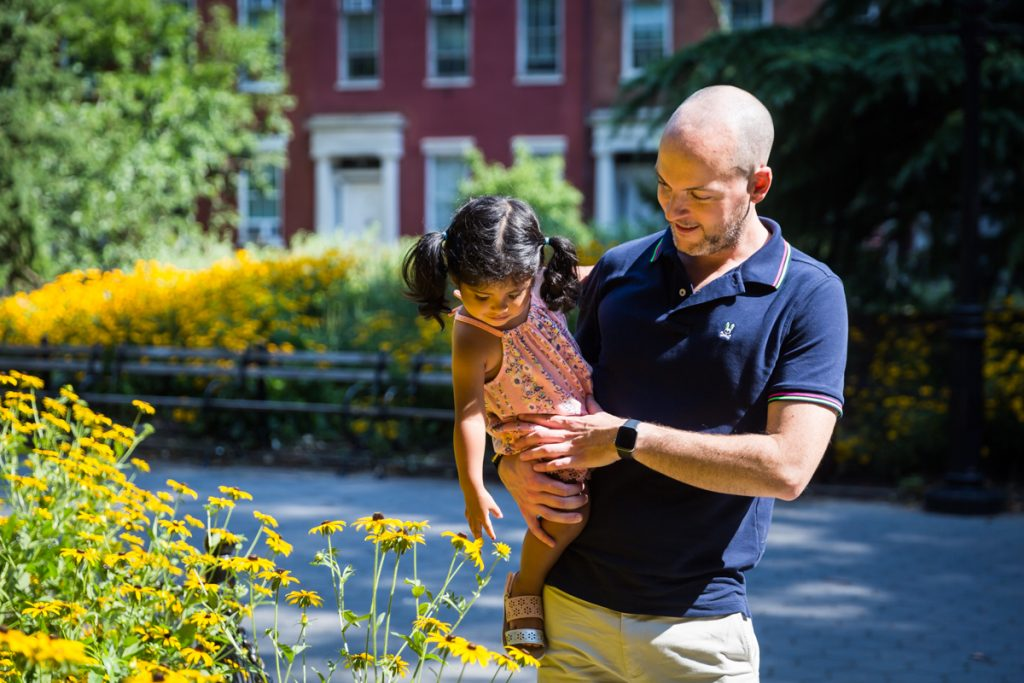 Father holding daughter over bush of yellow daisies