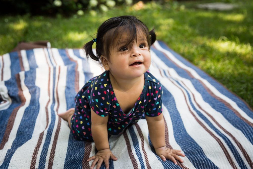 Toddler with pigtails crawling on striped blanket