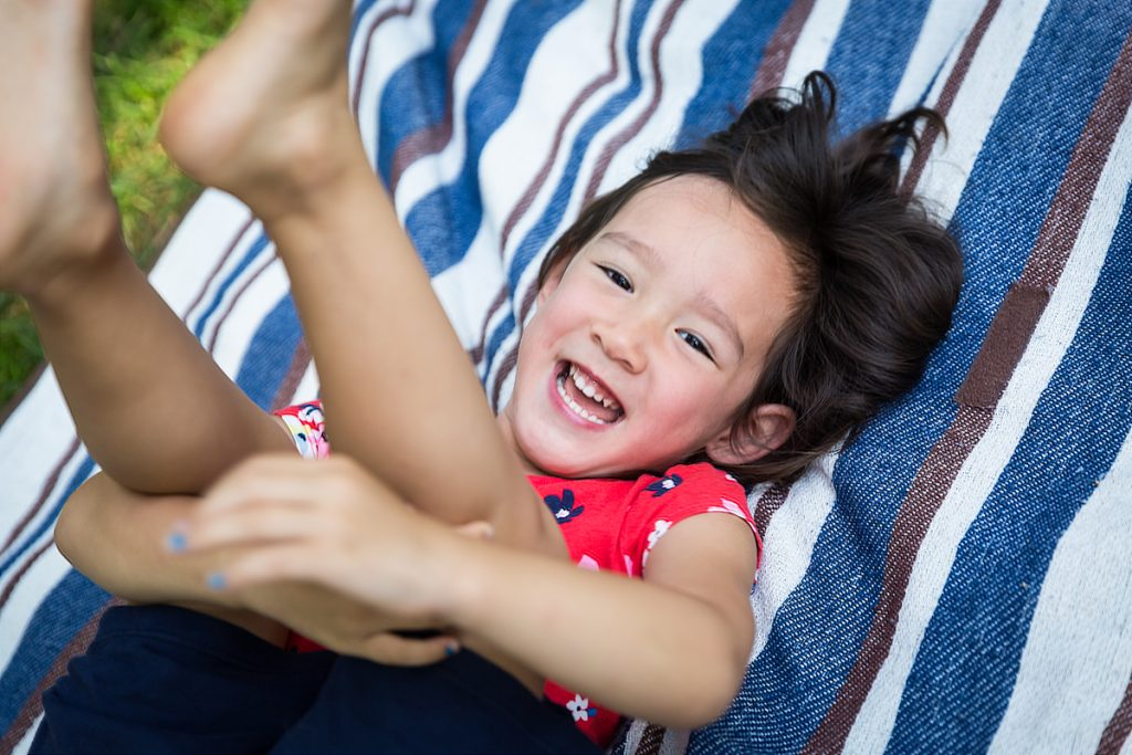 Laughing little girl playing on striped blanket