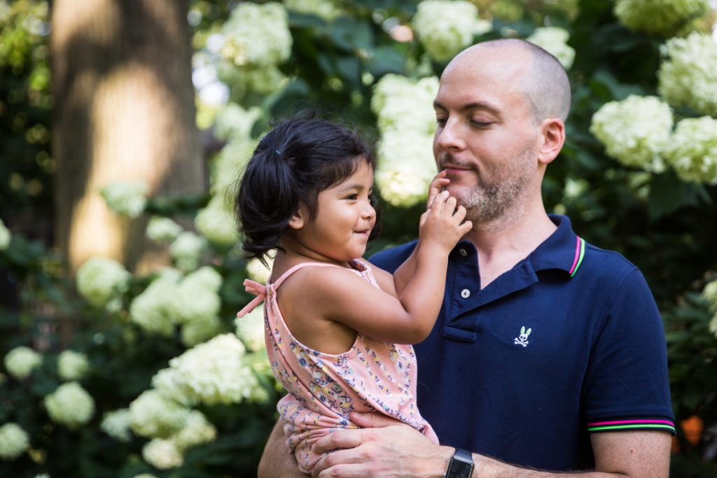 Father and little girl in front of hydrangea bush