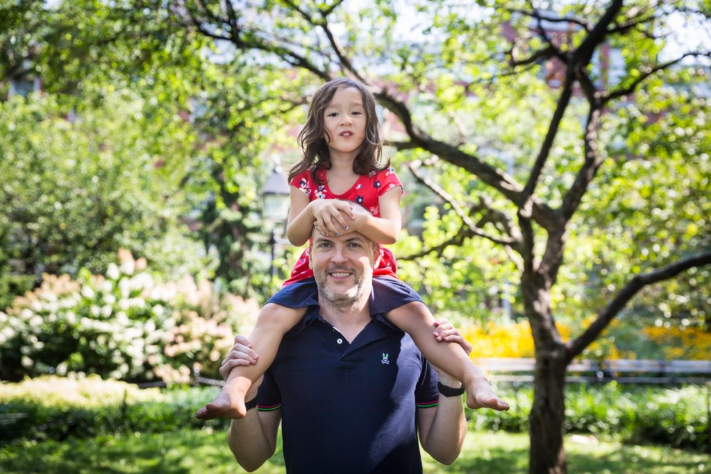 Father holding daughter on his shoulders during a Washington Square Park family portrait