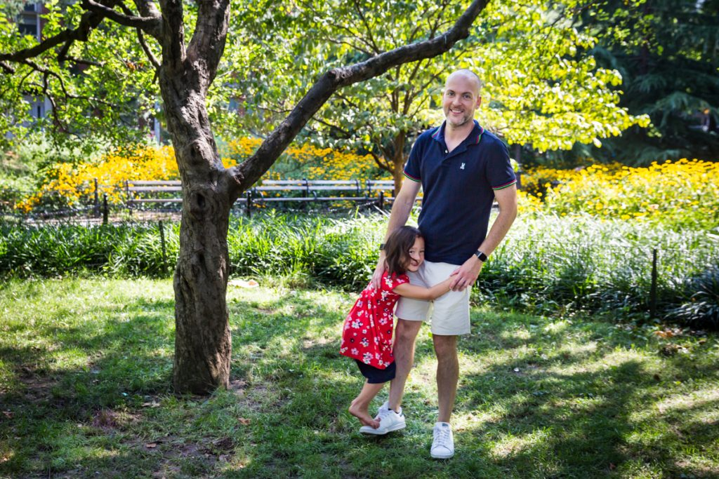 Father walking with daughter on his leg during a Washington Square Park family portrait