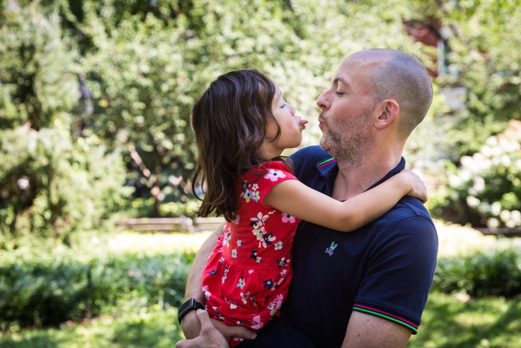 Father about to kiss daughter during a Washington Square Park family portrait