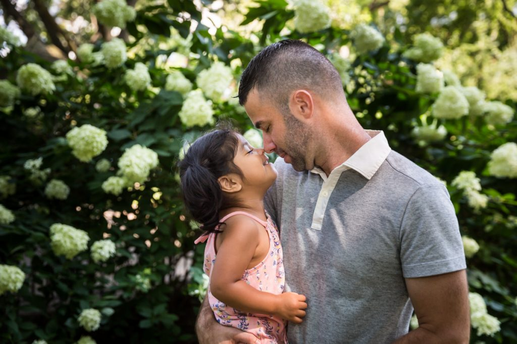 Father and daughter touching noses during a Washington Square Park family portrait