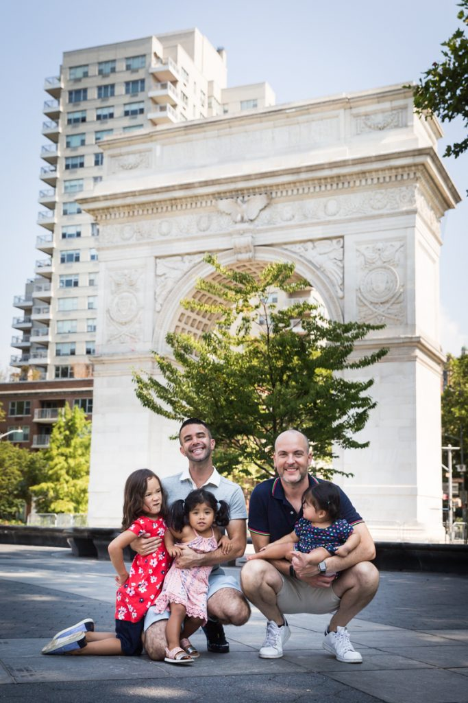 Two fathers and their three daughters in front of arch during a Washington Square Park family portrait