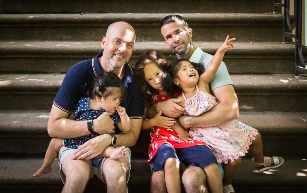 Two fathers and their daughters sitting on steps during a Washington Square Park family portrait