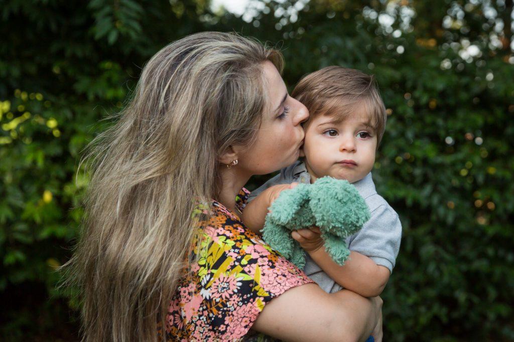 Mother kissing little boy on side of head in Hudson River Park
