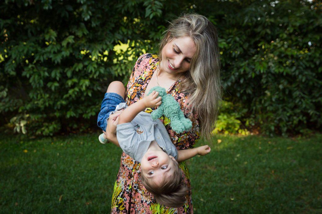Mother holding little boy upside down in Hudson River Park