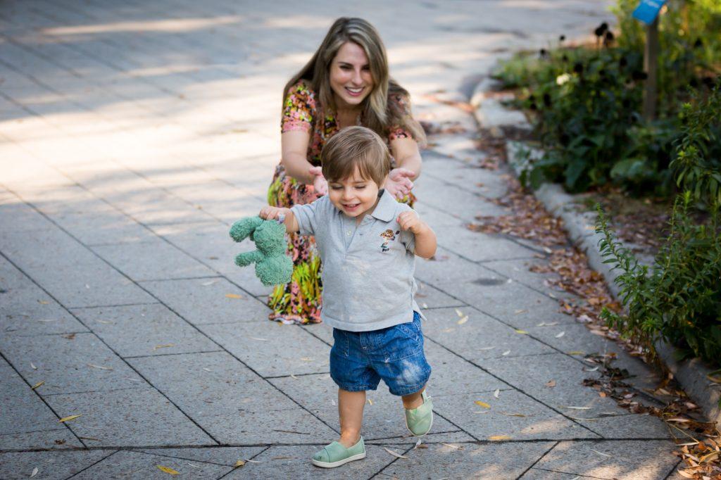 Little boy running from mother in Hudson River Park