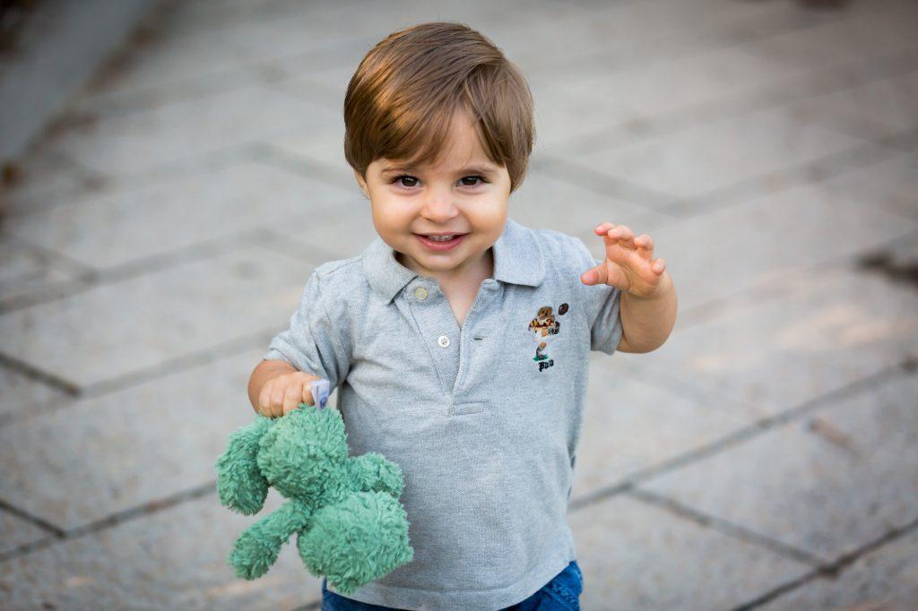 Little boy holding green stuffed animal in Hudson River Park