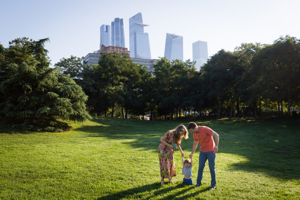 Parents holding little boy by the hand with NYC skyline during a Chelsea Waterside Park family portrait session