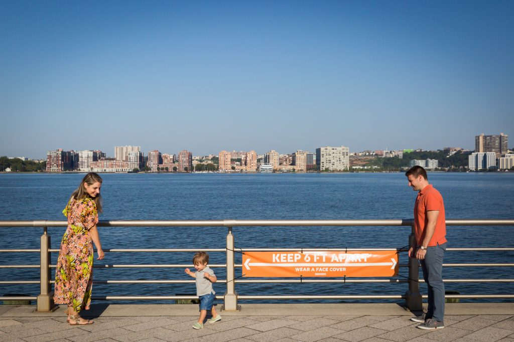 Parents and little boy standing in front of railing by Hudson River
