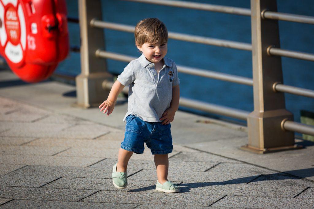 Little boy running in front of railing in Hudson River Park