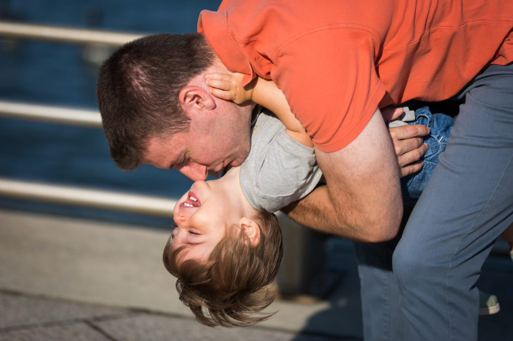 Father holding little boy upside down