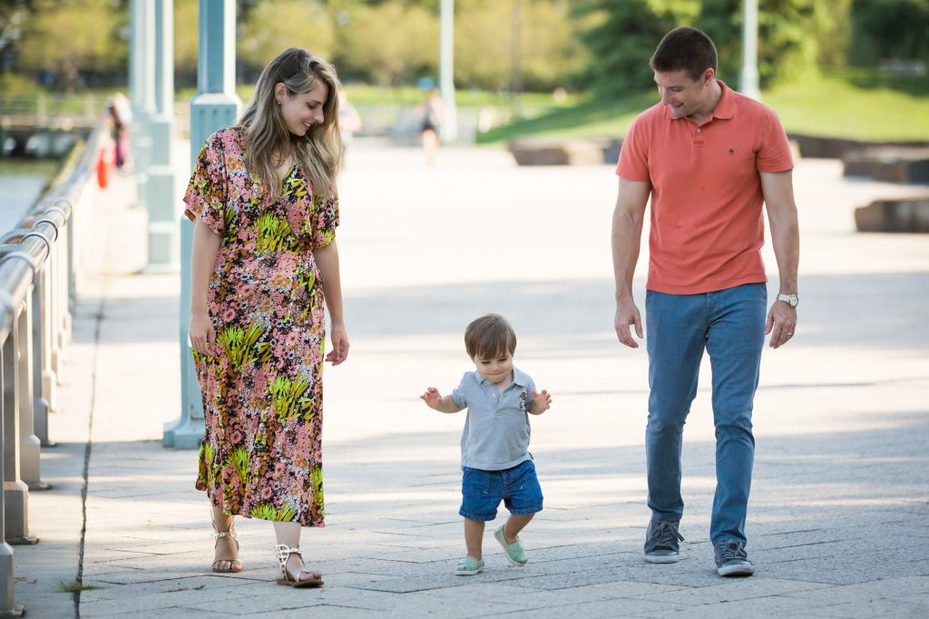 Parents walking along waterfront with little boy during a Chelsea Waterside Park family portrait session